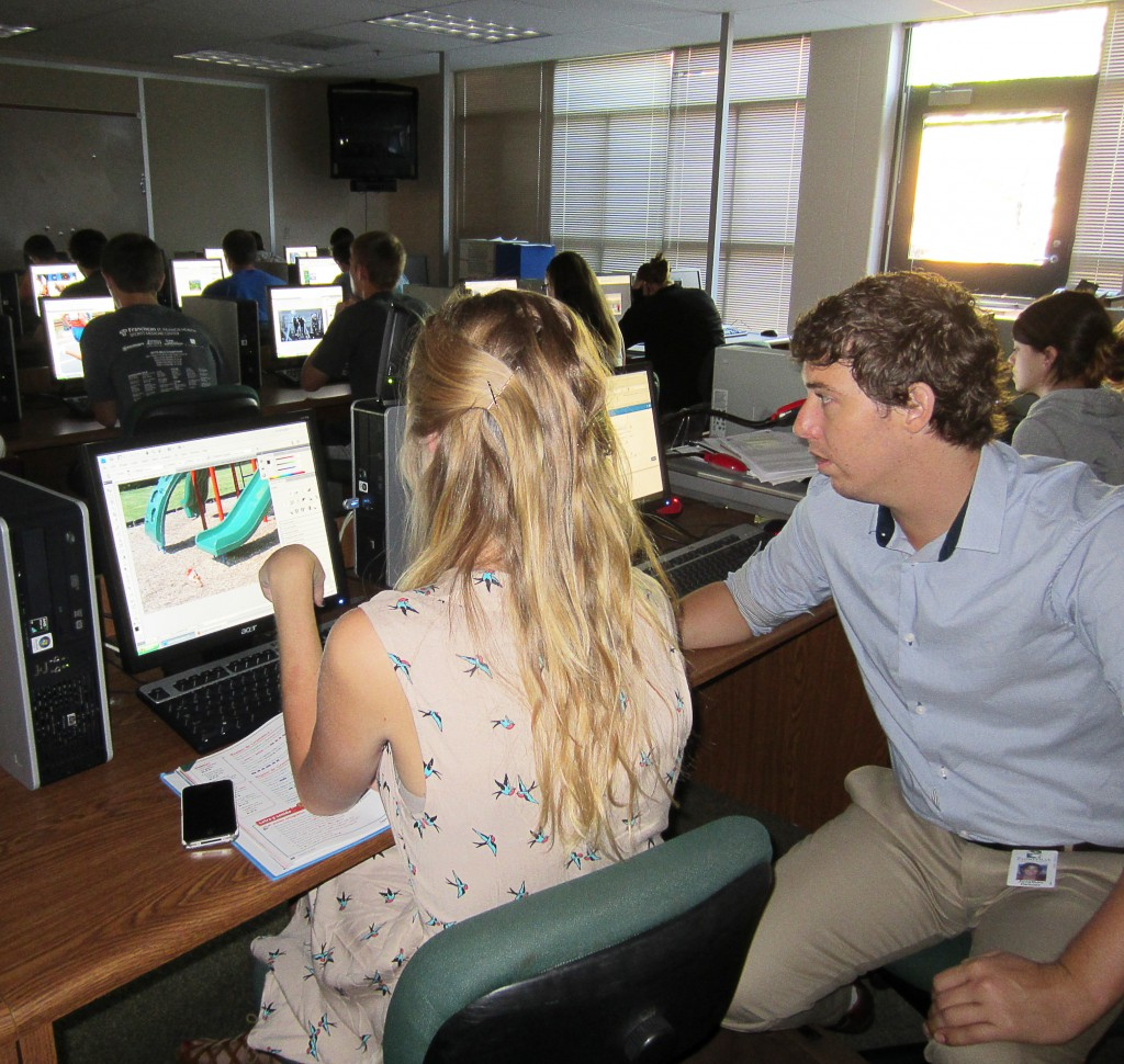 Expanding technology is a priority in 2013. Here, Mr. Jonathan Dehner, media art teacher, works with student in photography class.