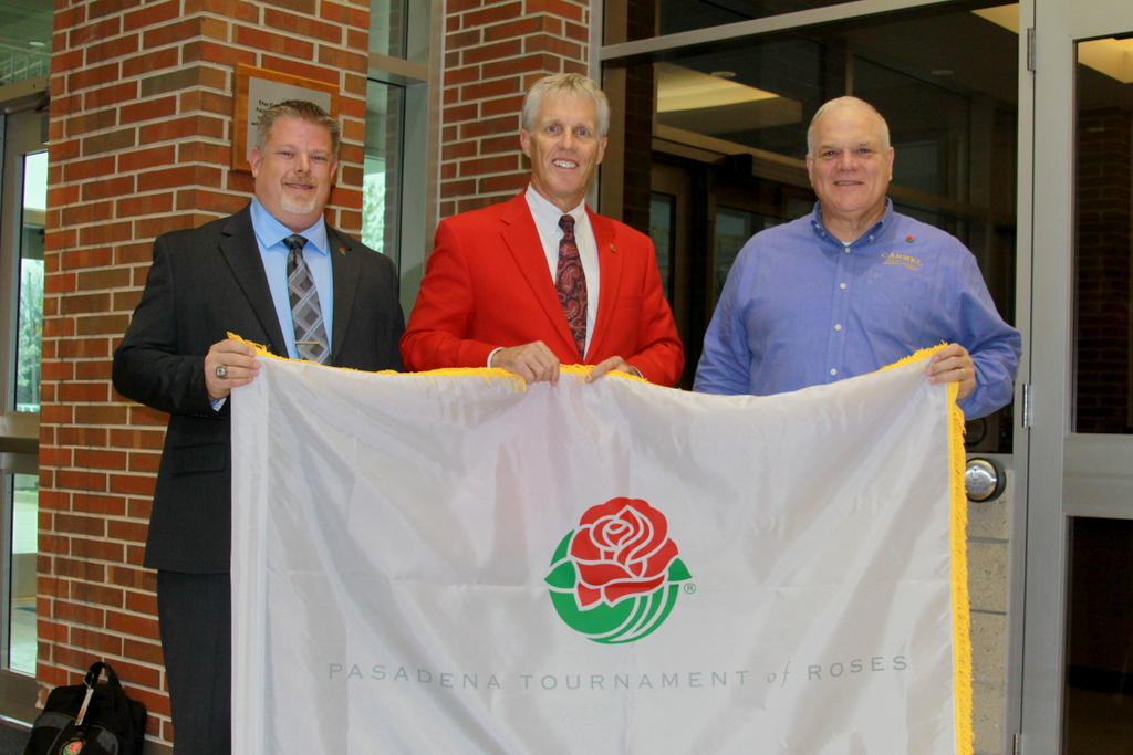 (from left) Christopher Kreke, Director of the CHS Marching Band, Scott Jenkins, president, Tournament of Roses and Dr. John Williams, Principal CHS High School stand behind the flag the Carmel High School Marching Band will carry in the parade.