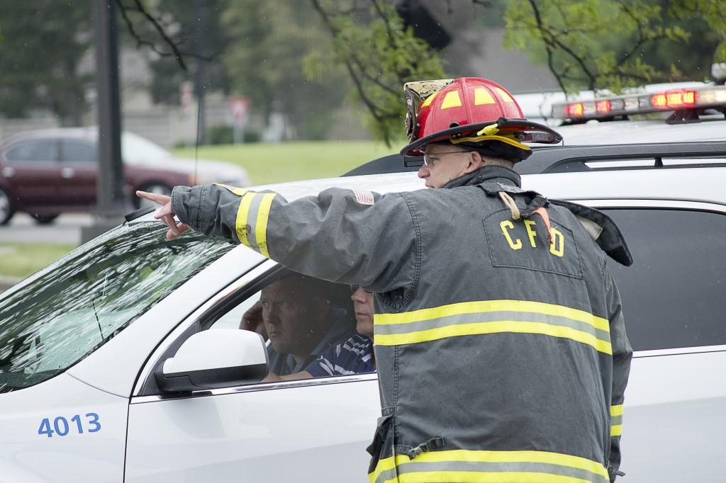 A member of the Carmel Fire Dept. directs employees of Vectren toward a gas line cut on Keystone Way on June 6. (Photo by Jillyann Burns)