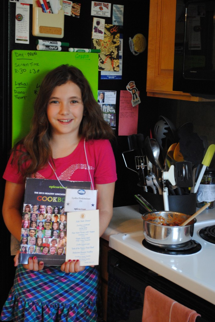 Lydia Finkbeiner holds her cookbook and menu from the First Lady's Luncheon, next to her award-winning chili