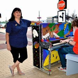 Carmel artist Nancy S. Peterson poses next to her creation while Kyle Curtis of the School of Rock plays it. (Photo submitted by City Center)
