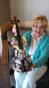 Carmel Symphony Orchestra patron and supporter Jeanne Book, holding her prized painted violin from the painted violins fundraiser. Staff Photo by Karen Kennedy