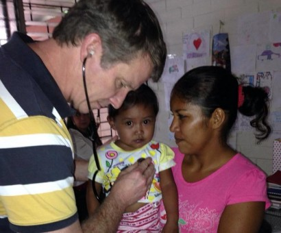 Dr. Chuck Dietzen helps a young girl in El Salvador. (photo by Jeff Cardwell with People Helping People Network)