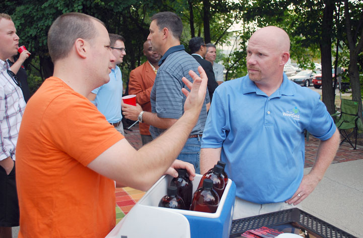 """Brewer Brian Graham of Four Day Ray, left, talks with Kenneth Alexander, Westfield's public works director, while dispensing samples of his beer during the Downtown Westfield Association's """"Party on the Patio"""" on Sept. 18. (file photo by Robert Herrington)"""