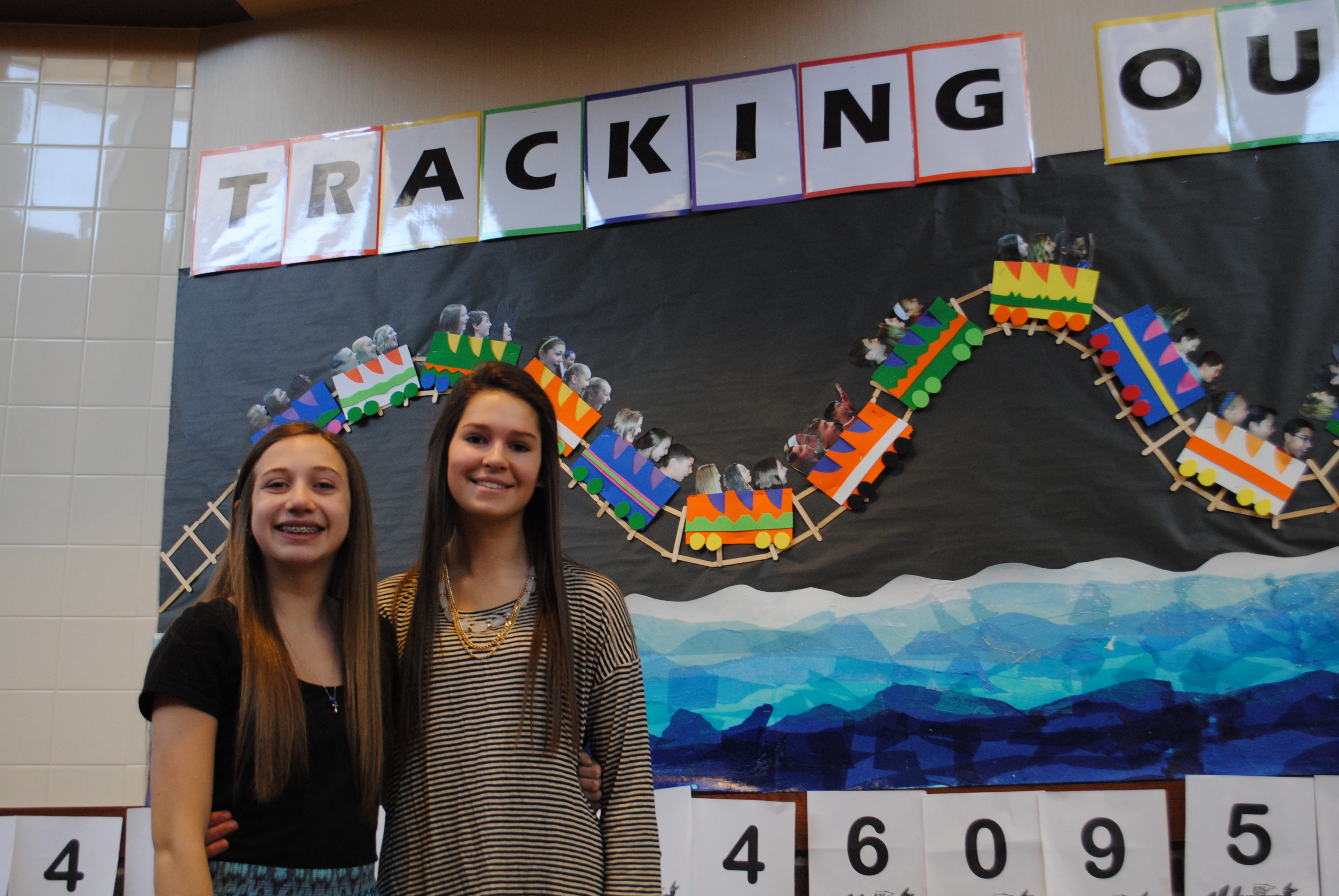 Ellie Avagian, left, and Kylie Kuchik were chosen to represent the science classes of Clay Middle School. The students in the science classes raised more than $4,000 for relief efforts related to Hurricane Sandy, which devastated parts of the east coast in 2012. Shown behind the students is a portion of the numeral Pi. (Staff photo)