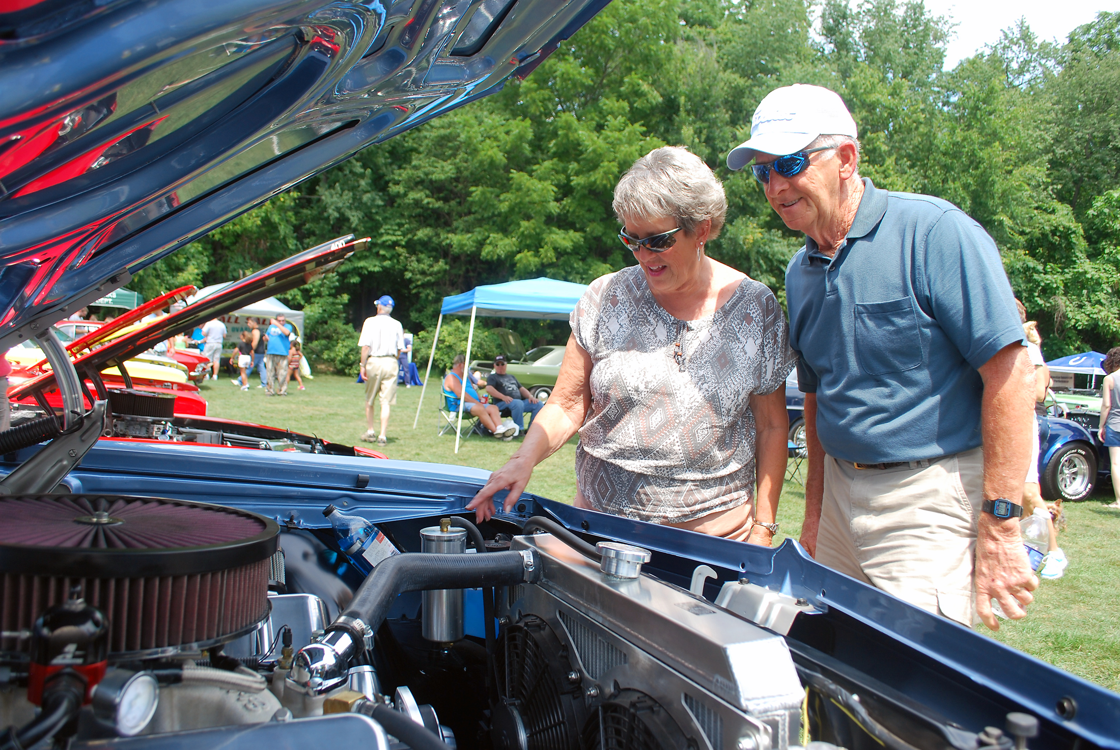 Sue and Jim Morris inspect the engine of Nathan Gale's 1965 Chevy Impala. (File photo)