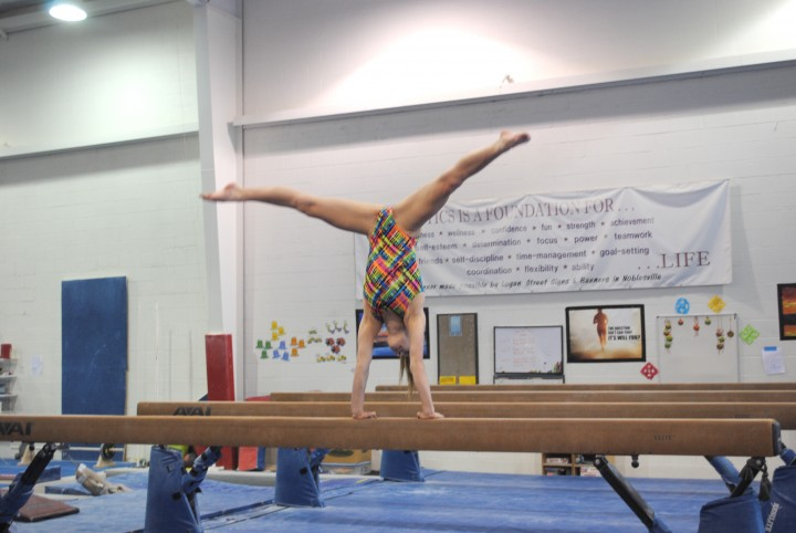 Mia Lord practices on the beam (Photo by Mark Ambrogi)
