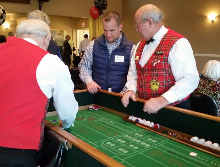 Adam Filler, a HAND board member, receives advice from a Sertoma volunteer while playing Craps. (Submitted photo)