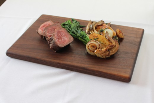 The Loft's grass-fed strip loin steak served with fingerling potatoes, Cipollini onions, oyster mushrooms and broccoli rabe.