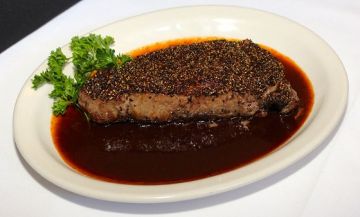 Harry and Izzy's peppercorn crusted New York Strip steak resting in Izzy sauce.