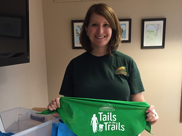 """Zionsville Nature Center manager Mindy Murdock displays the bandana given to participants who complete the program and the """"Wag Bag"""" participants receive by registering. (Photo by Anna Skinner)"""