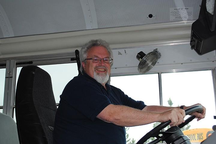 Tom Miller test drives a school bus. (Photo by Mark Ambrogi)
