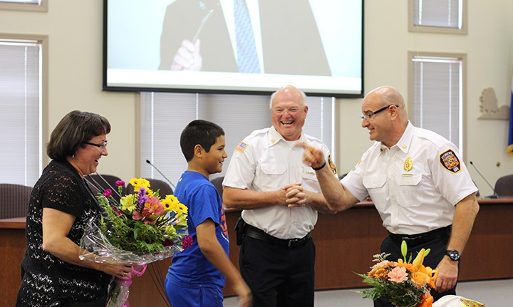 Fishers Fire Chief Steve Orusa, right, talks with Fishers Fire Marshal Brian Lott and the Lott family during Lott's retirement party on Oct 12. (Photo by James Feichtner)