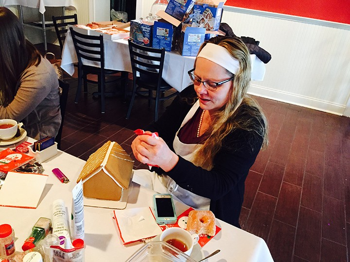 Beth Aasen, owner of Donatello's Italian Restaurant, makes a gingerbread house.