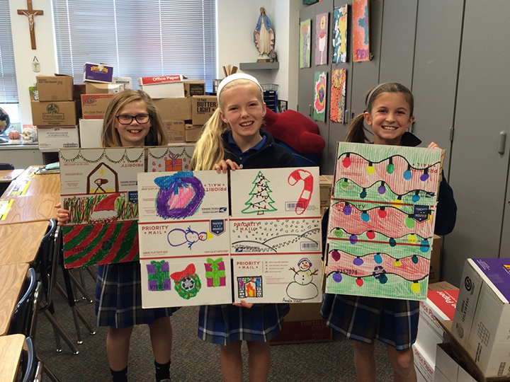 St. Simon students hold up their decorated boxes they will use to ship extra Halloween candy to military troops overseas. (Submitted photo)