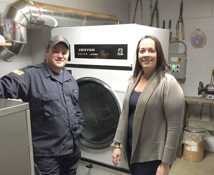 Captain Steve Moore and Trustee Danielle Carey Tolan with the new gear wash extractor and dryer and Westfield Fire Station 82. (Submitted photo)