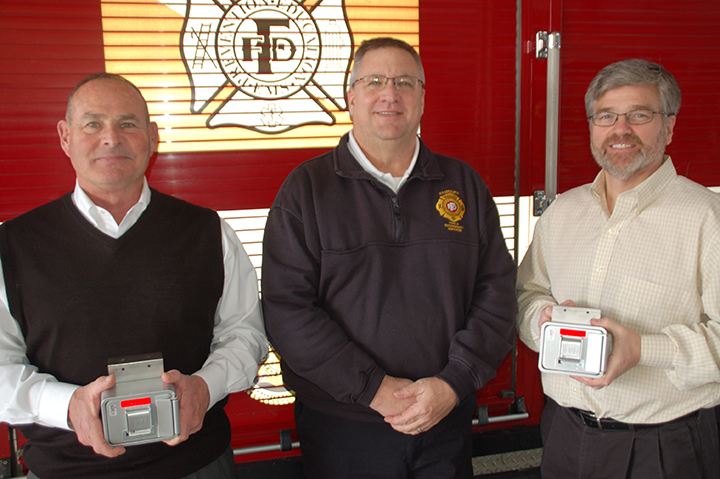 From left, Meyer Najem Chief Strategy Officer Sam Mishelow, Fishers Fire Dept. EMS Chief Steve Davison and Meyer Najem Chief Financial Officer Robert Lawyer with the two Knox Box key systems Meyer Najem's donation provided. (Submitted photos)