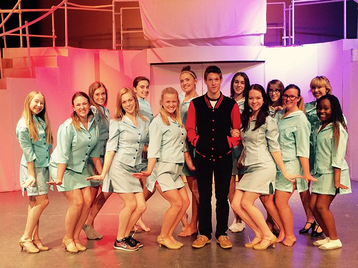 """Conner O'Leary, surrounded by fellow FHS performers portraying airline stewardesses, plays the lead role of Frank Abagnale in the school's production of """"Catch Me If You Can."""" (Photo by Mark Ambrogi)"""
