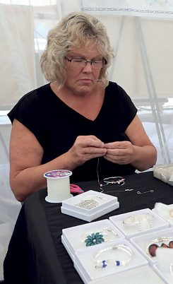 Cindy Andrews of The Cross-Eyed Cow Beaded Jewelry works on jewelry at the 2015 market. (File photo)