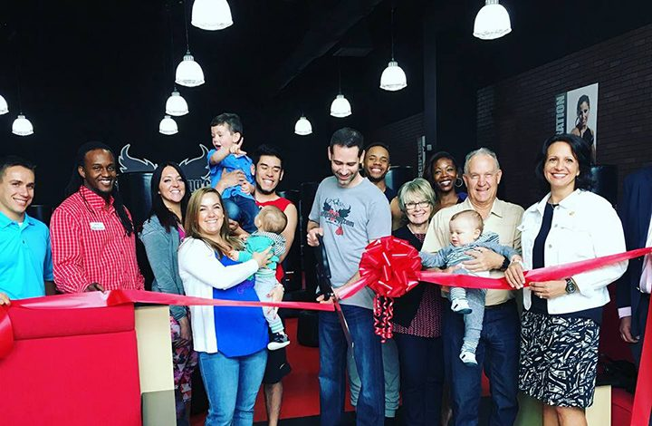 Travis Watson, center, cuts the ribbon at the grand opening of his iLoveKickboxing studio. (Submitted photo)