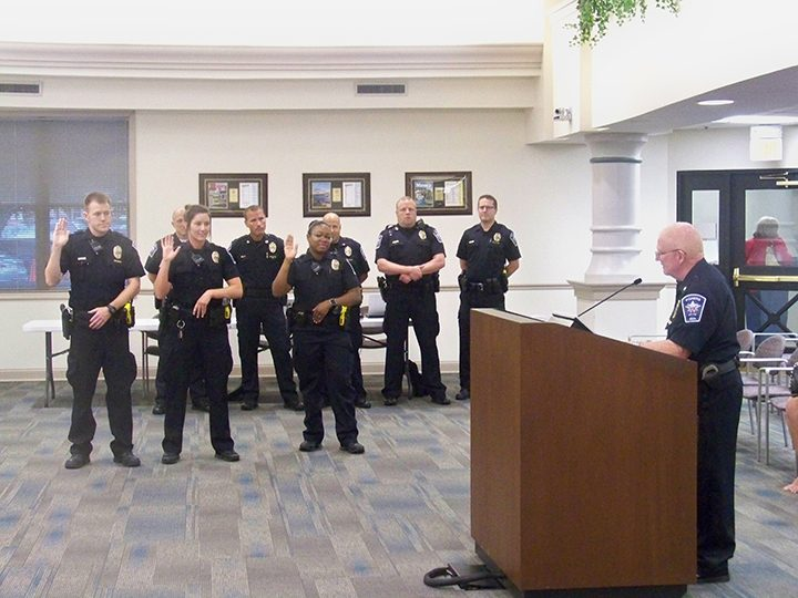 Fishers Police Chief George Kehl, right, swears in new Fishers Police Dept. officers, from left, Jonathan Dossey, Brianna Guy and Dynesha Harris during the June 20 Fishers City Council meeting at city hall. (Photo by Sam Elliott)