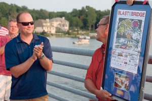 Fishers Mayor Scott Fadness presents an award to Geist Lake Coalition President Brian Hall for his work with the organization, which uses Blast on the Bridge as a fundraiser for its reservoir water cleanup initiatives.