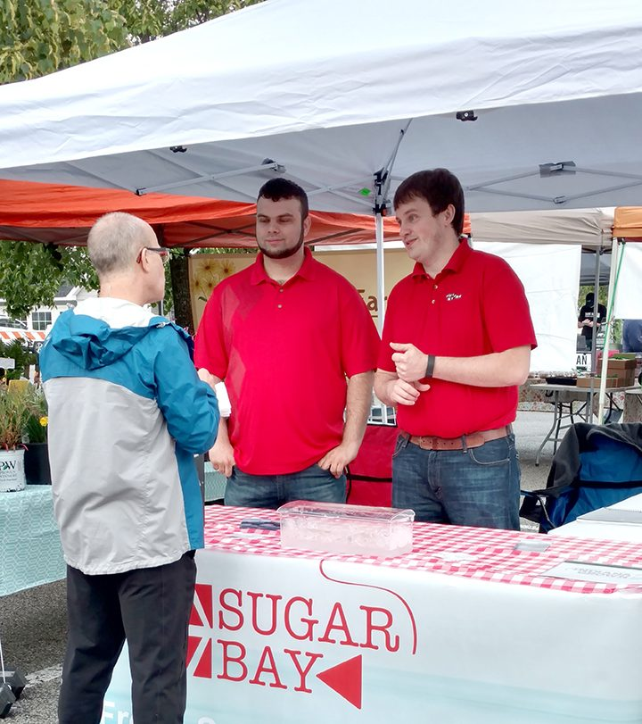 Travis Wright and John Padgett share their story with a customer at the Zionsville Farmer's Market. (Photo by Heather Lusk)