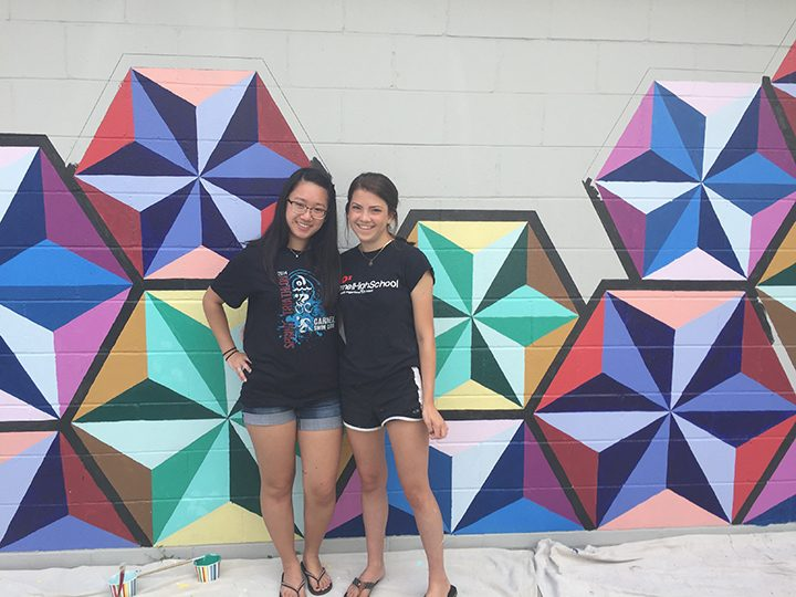 Dana Wang, left, and Katy Voor designed the mural on the west wall of Carmel Tattoo INK, 43 W. Main St. (Photo by Anna Skinner)