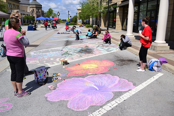 Onlookers watch at chalk artists get creative at Hamilton Town Center. The Chalk Art Festival returns this month for the third year. (File photo)