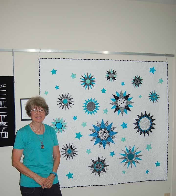 """Judy Pleiss shows the Mariner's Compass block quilt titled """"Never say never."""" (Photo by Heather Lusk)"""