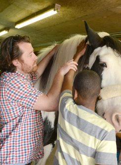 ISBVI Social studies teacher Josh Baxter helps fifth grader Kentrell Parker pet a horse. (Photo by Theresa Skutt)