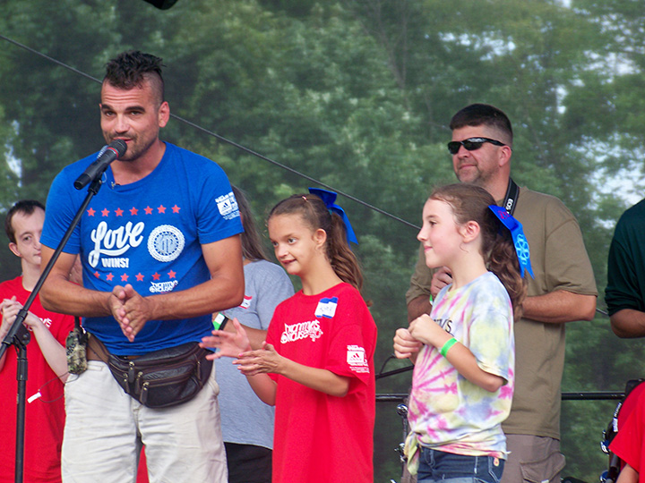 Fortville resident Jared Hiner introduces his daughters, Kamdyn and Sophia, to the crowd at Kammy's Kause, a two-day music festival and fundraiser for the 4p- Support Group. Kamdyn, 14, was diagnosed with 4p-, a rare chromosome disorder, when she was one-moth old. (Photo by Sam Elliott)