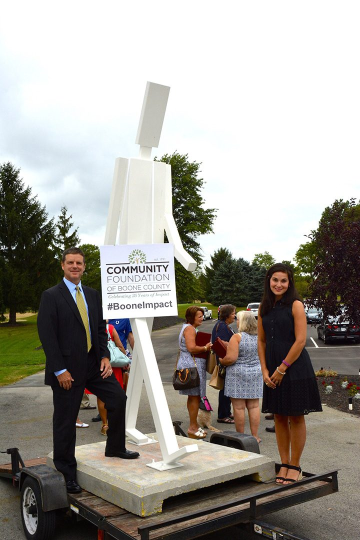 Zionsville Mayor Tim Haak and Director of Communications Amanda Dorman with one of the five Walking Man sculptures. (Submitted photo)