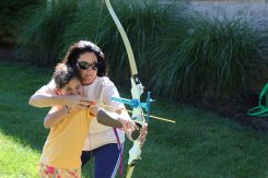 Susana Suarez helps her daughter, Eva, shoot at a target in the yard at their Zionsville home. (Photo by Ann Marie Shambaugh)