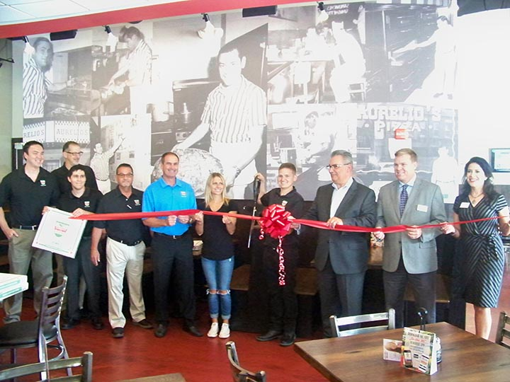 Local and corporate Aurelio's staff members are joined by Fishers City Council members to celebrate the grand opening of the new Fishers restaurant. On the wall are photos from the original Aurelio's founded in 1959 in Homewood, Ill. (Photo by Sam Elliott)