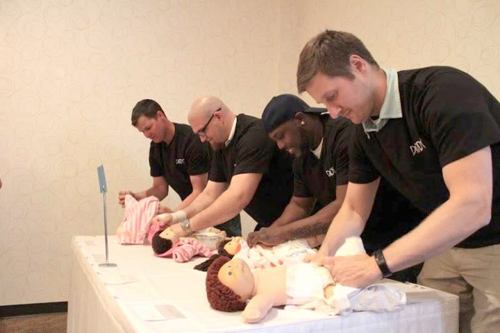 Daddy-a-Thon participants work to dress a baby doll. (Submitted photo)