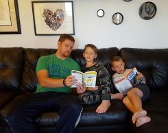 """From left, Michael, Owen and Christopher Lutomski read """"The Lemonade War."""" (Submitted photo)"""