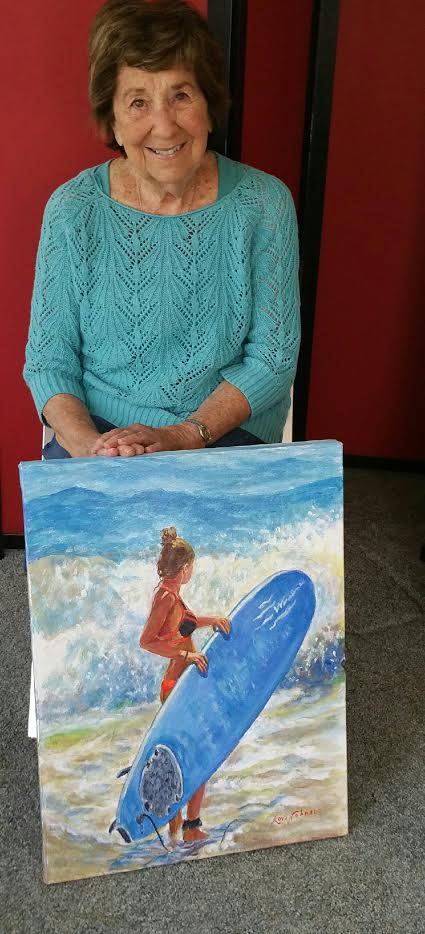 Artist Lori Johnson with one of her recent paintings. (Photo by Heather Collins)
