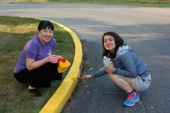 Miki Kasamatsu and Mia Yuda from Japan paint the curb at the Boys & Girls Club. (Photo by Heather Lusk)