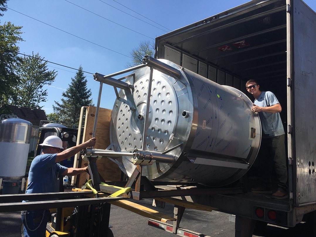 """Bobby Mattingly unloads the brewing equipment on a hot summer day in 2017. """"We worked through the night and brought everything in one piece at a time,"""" Bobby said."""